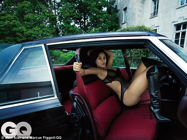 Kicking up her heels: The reality star wore kinky boots and a cut-out body suit while posing in a vintage car