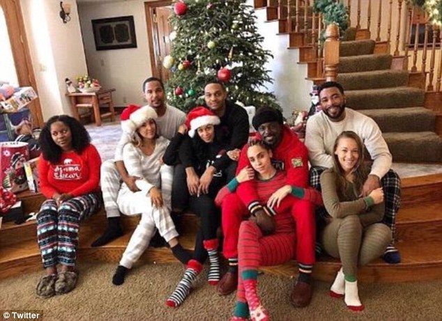 Lance Gross and his wife, Rebecca (seen second from right) take a Christmas photo with friends. The image shows four couples and one woman conspicuously alone and off to the side